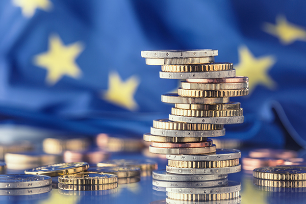 Euro coins in front of a eu flag - Halo Financial