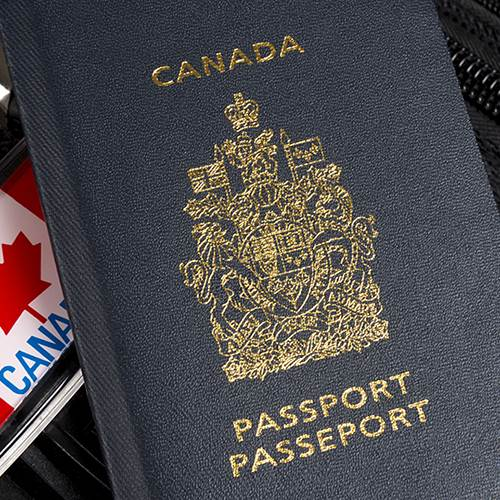 Canadian passport sitting on suitcase