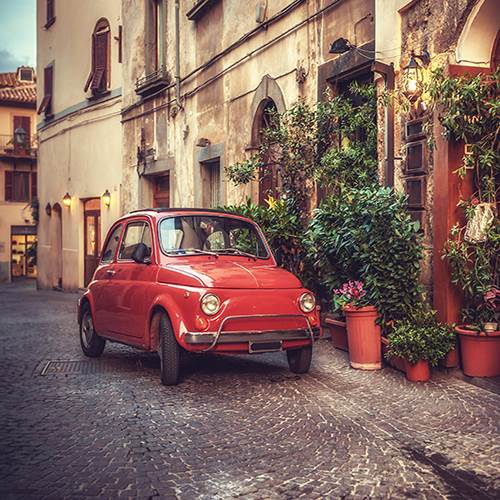 Old vintage cult car parked on the street Italy