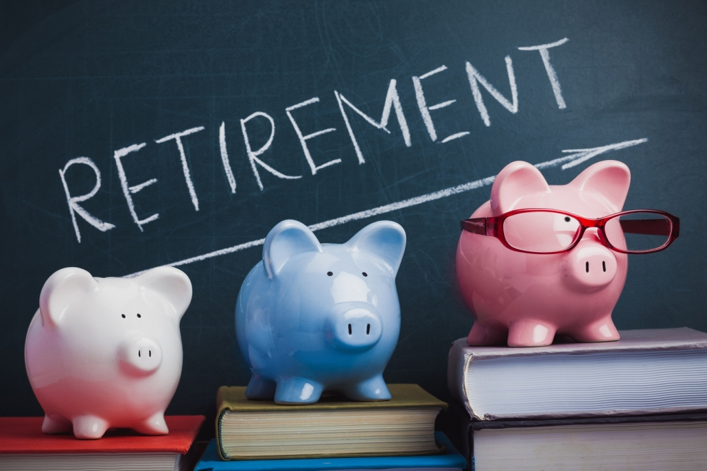 3 piggy banks on top of a book. A blackboard on the background with retirement written in chalk. Retiring abroad concept.
