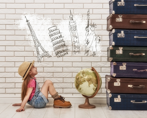 happy child girl against a white brick wall. girl having suitcases and dreaming of traveling. Moving abroad alone concept.