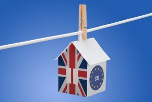 Britain flag and EU flag painted on a paper house hanging on a rope, symbolising Brexit impact on overseas property.