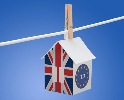 Britain flag and EU flag painted on a paper house hanging on a rope, symbolising Brexit vote impact on property purchase