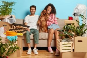 taking pet abroad concept. Happy diverse couple sit on sofa with favourite dog, have break on moving day, busy unpacking, have mess in new flat, many packages, remove to own house
