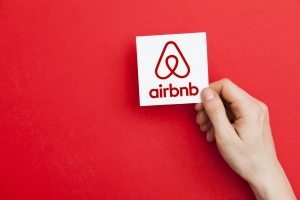Hand holding Airbnb logo. Airbnb is a popular online home vacation rental company