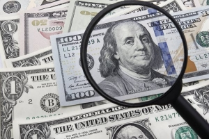 USD dollar and a magnifying galss - US focus on today's data