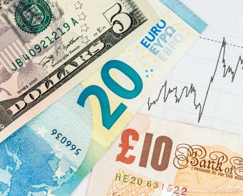 Euro Dollar and Pound banknotes with a chart in the background symbolising economic data from UK Euro and US concept of recent events affecting currency markets