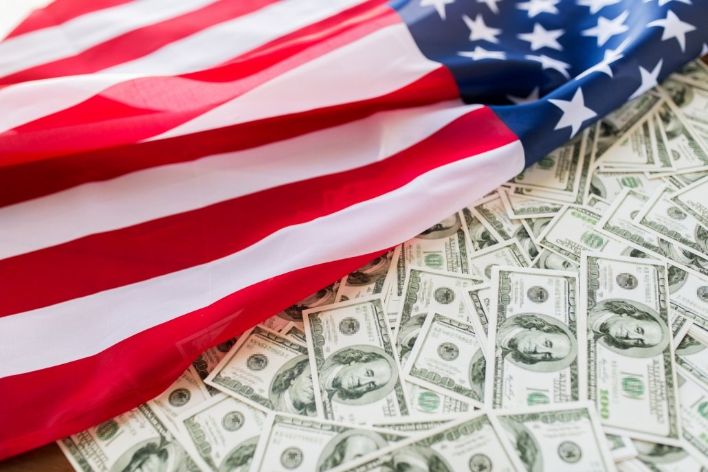 US Dollar banknotes covered by USA flag