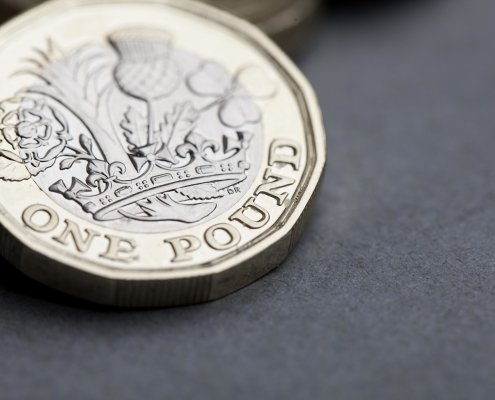 New British one pound sterling coin. Pound rises on economic data concept