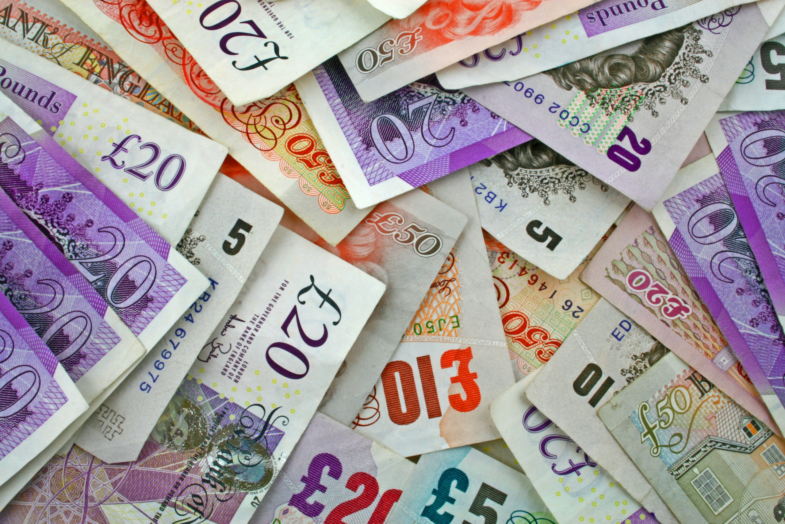 pile sterling notes sprawled out symbolising Sterling and UK economy